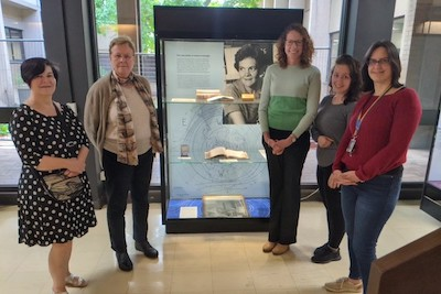 Prominent women in the School of Physics standing beside a display memorialising Dr Jean Laby, the first female PhD graduate from the school.